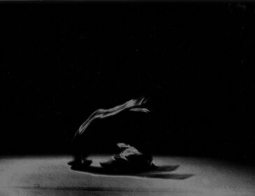 Black and white photograph of a form on stage in silky material