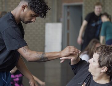 Male dancer of South Asian descent interacts with white female wheelchair dancer