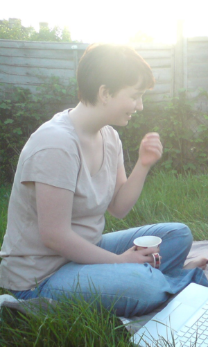 a white woman with short red hair sits cross legged in long grass. She is wearing a beige t-shirt, jeans and no shoes. In one hand she's holding a cup of tea