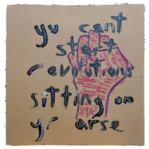 Artwork done on cardboard with a clenched red fist and the words you can't start revolutions sitting on your arse painted in black