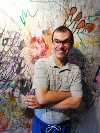 An artist is stood in front of his large scale work which fills the whole background behind him. He is wearing blue trousers and a beige polo shirt with horizontal stripes. The piece of work behind him is a collection of colourful expressive marks on a white background