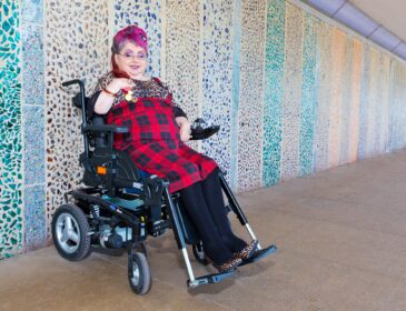 Penny Pepper a wheelchair using white woman with pink hair sits against a colourful wall