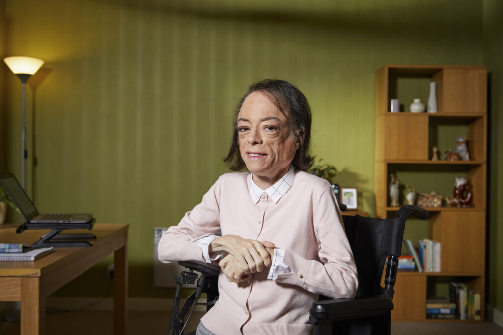 Portrait shot of a white disabled actress in a wheelchair wearing a pink cardigan, sitting in a living room
