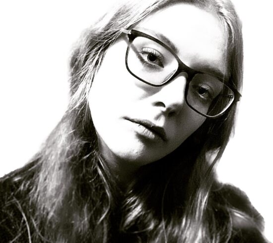 A black and white photo of a 27 yr old white female, Ellie Page. She has long, light hair and black-rimmed square glasses. She is looking up to face the camera and looking rather stern.