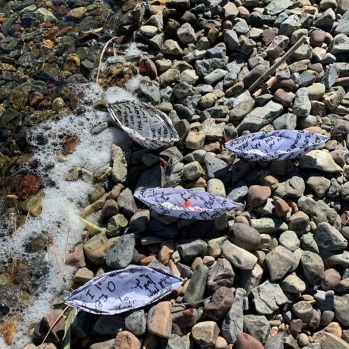photo of four paper boats on the edge of water