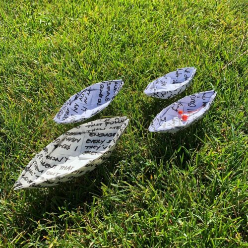 photo of four paper boats on grass