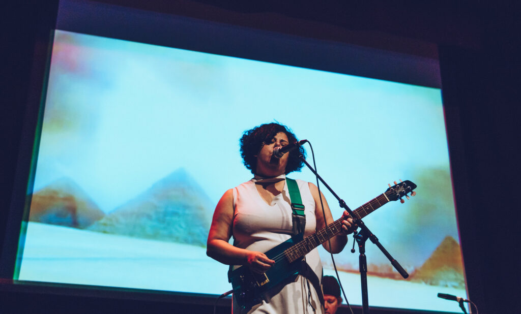 Woman of colour playing a guitar against a backdrop of a projected pyramid