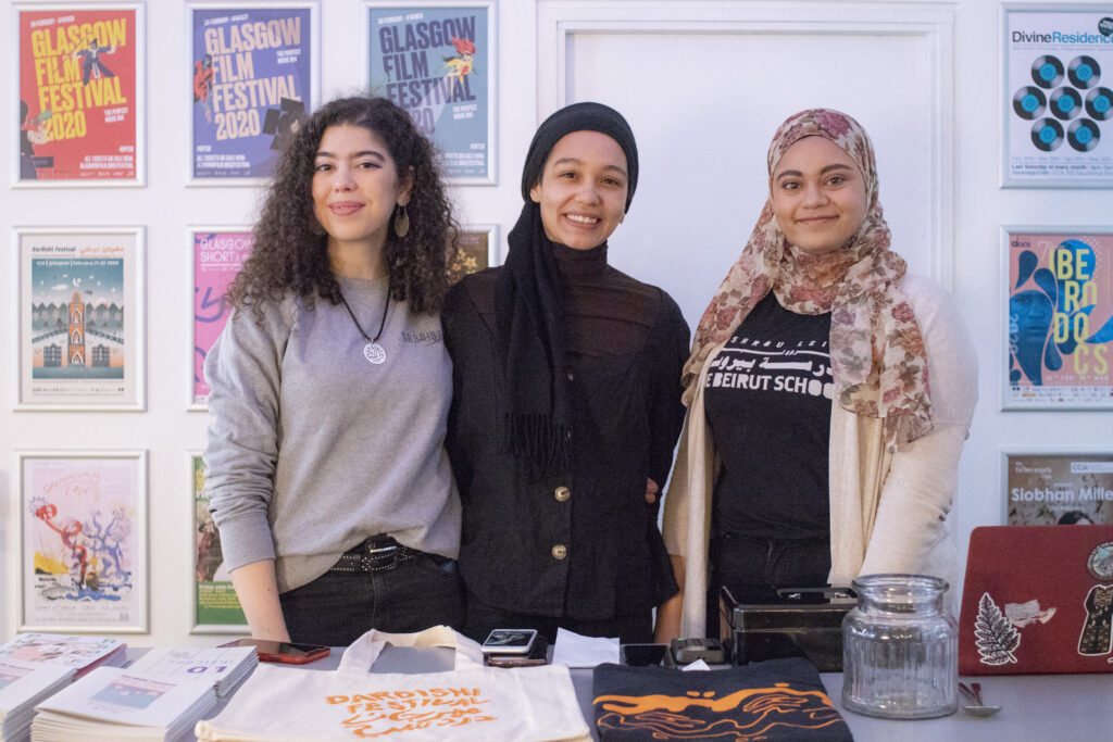 3 young Arab women, two wearing headscarves, stand in front of a table smiling