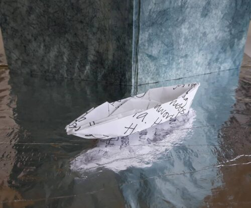 Photo of a paper boat reflected on water