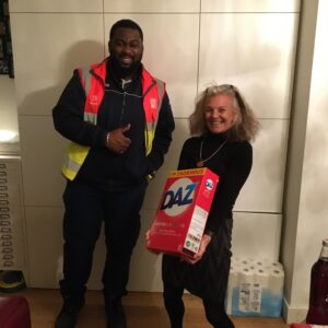 Black male Tesco delivery driver gives a thumbs up while a white woman in her 50s holds a huge box of washing powder