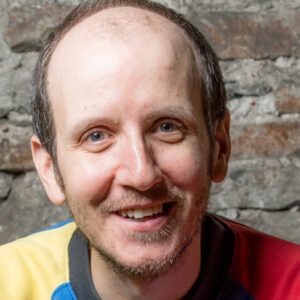 A white man with balding brown hair, blue eyes, smiling