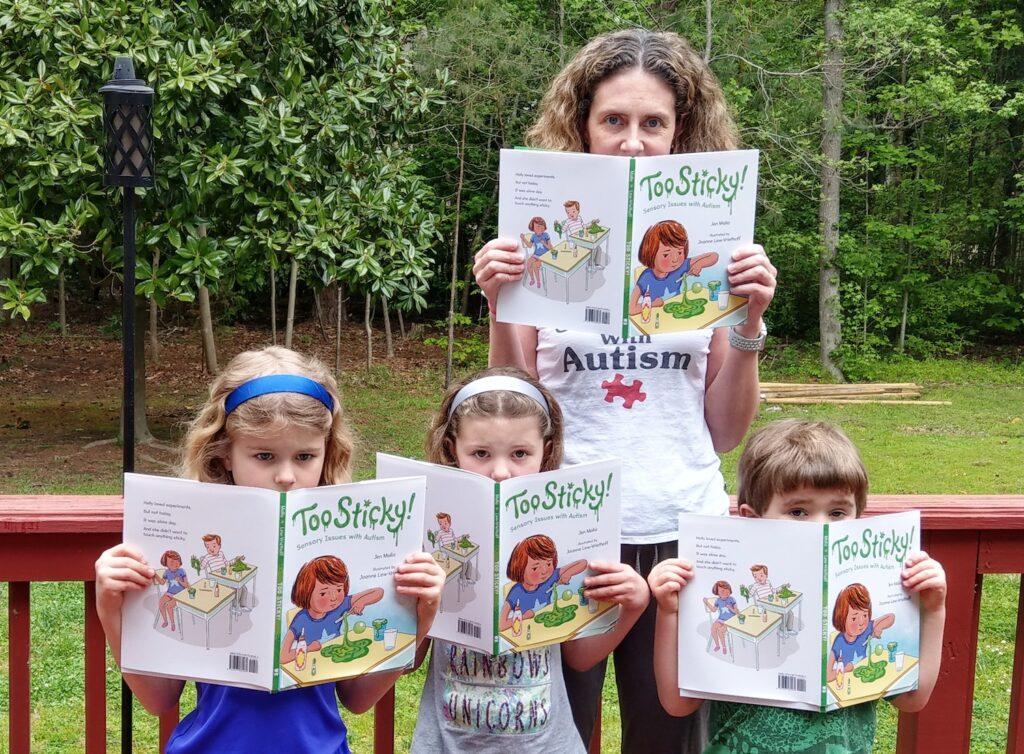 photo of the author and her three children in their garden each with a copy of the children's book 'Too Sticky'