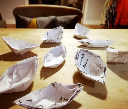 Photo of nine paper boats on a table top