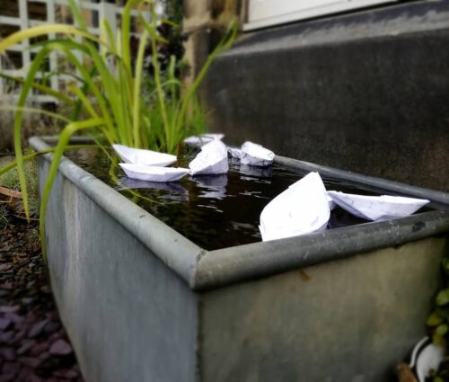 Photo of paper boats in a metal bath with reeds