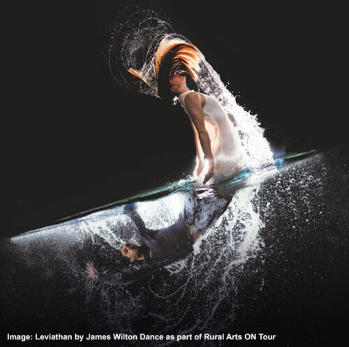 A male and female dancer perform with a black background as reflections of each other with water splashing dramatically around them