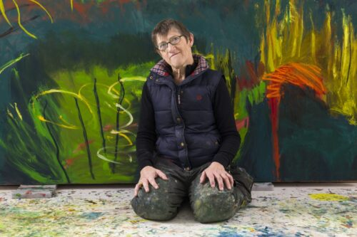 A photograph of a lady in glasses kneeling down on the floor with a large brightly coloured painting behind her
