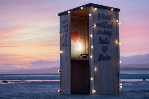 A photo of a wooden hut on a beach at sunset. The hut is covered in a string of lights and has 'I just called to say Isle ♥ Bute' written on the side. There is a light inside and a telephone on a worktop.