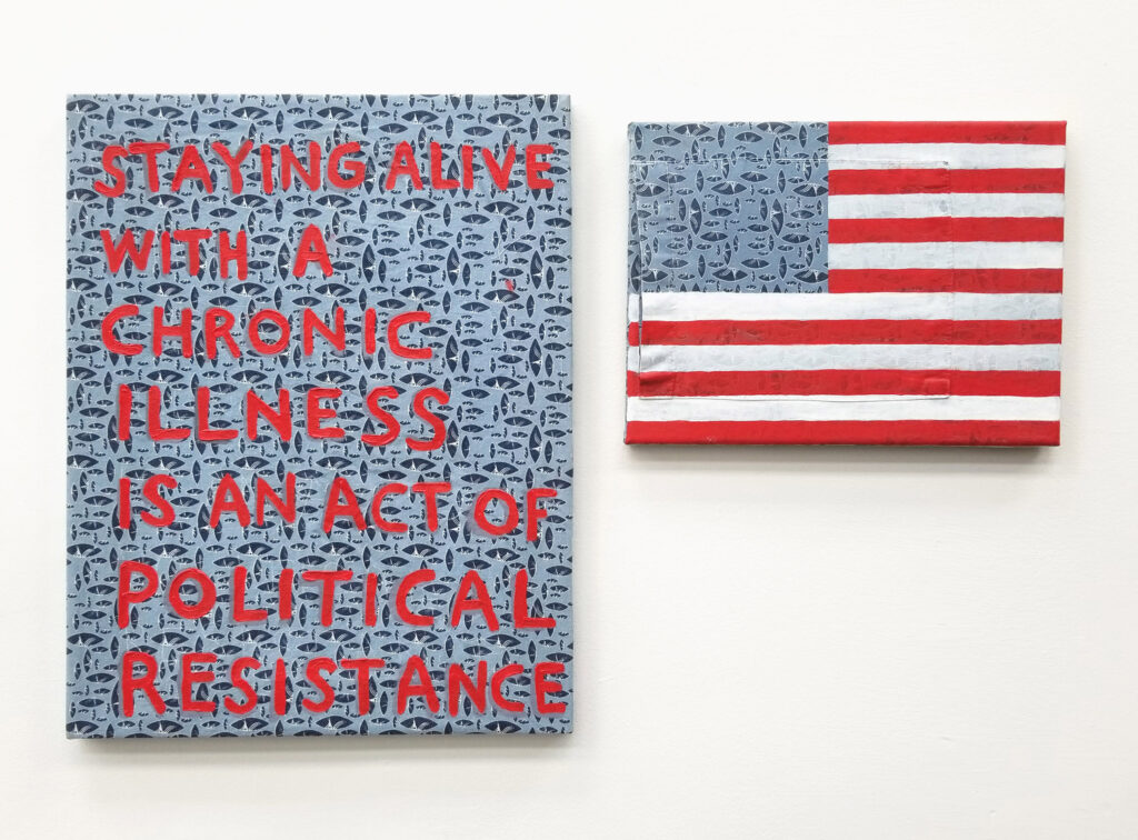 photo of red text that reads: Staying alive with a chronic illness is an act of political resistance. On a fragment of blue hospital gown next to a US flag