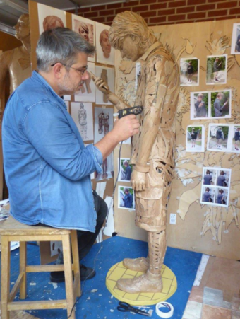 Man sitting on a stool in a blue denim shirt, holding a glue gun and sticking cardboard onto a cardboard sculpture of a figure