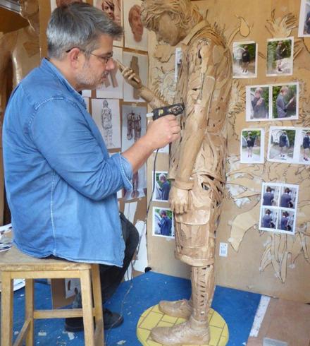 Man sitting on a stool in a blue denim shirt, holding a glue gun and sticking cardboard onto a cardboard sculpture of a figure
