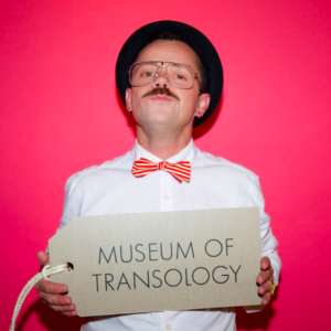 "photo of a person with a large label which says ""museum of transology'"