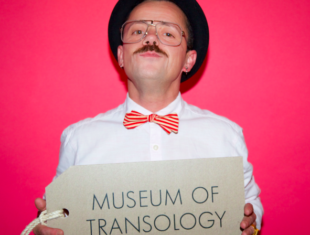 """photo of a non-binary person with a large label which says """"museum of transology'"""