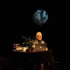 Photo of a white male artist sitting behind a laptop, in a darkened setting - an image of the earth above him
