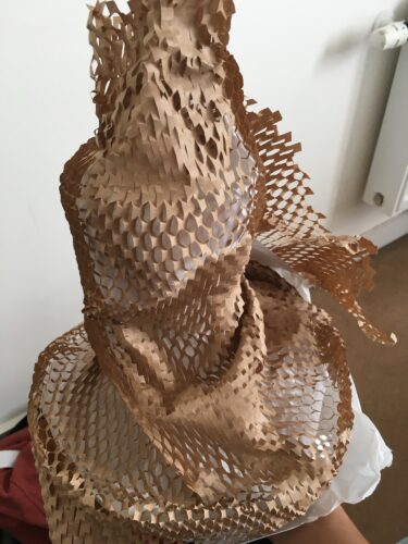 Digital image of crinkly brown packing paper with a netted/honeycomb pattern cut into it.