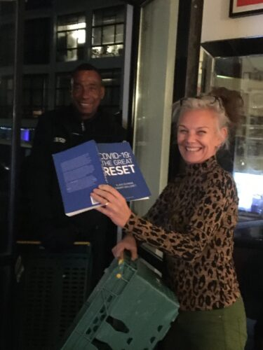 White woman in her 50s stands holding a green crate and a book called the great reset, while a black Tesco delivery man stands at the door