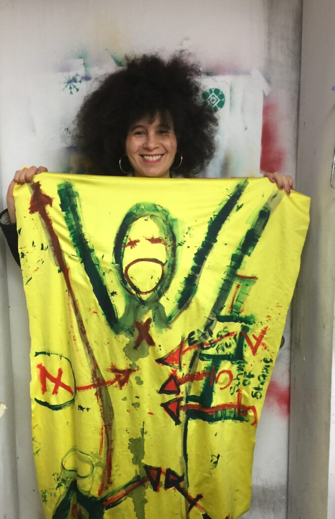 Photo of a black woman holding up a canvas with a figurative painting on it