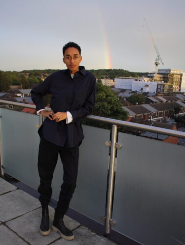 Photo of a young black writer pictured full-length, standing on a balcony