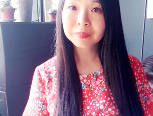A woman of east-Asian descent with long black hair wearing a red dress