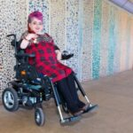 enny Pepper a wheelchair using white woman with pink hair sits against a colourful wall