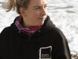 A white woman with blonde heair wearing a black Disability Arts Online hoody stands smiling on a beach