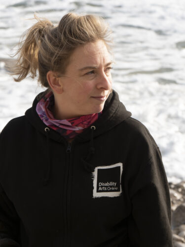 A white woman with blonde hair wearing a black Disability Arts Online hoody stands smiling on a beach