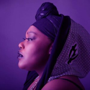 headshot of a Black songstress taken from a side profile
