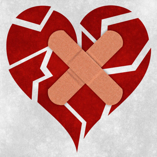 Cartoon image of a broken heart with two plasters on it