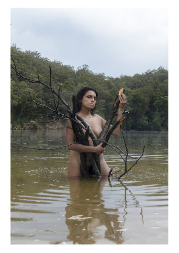 portrait of a disabled woman of colour, standing in a lake