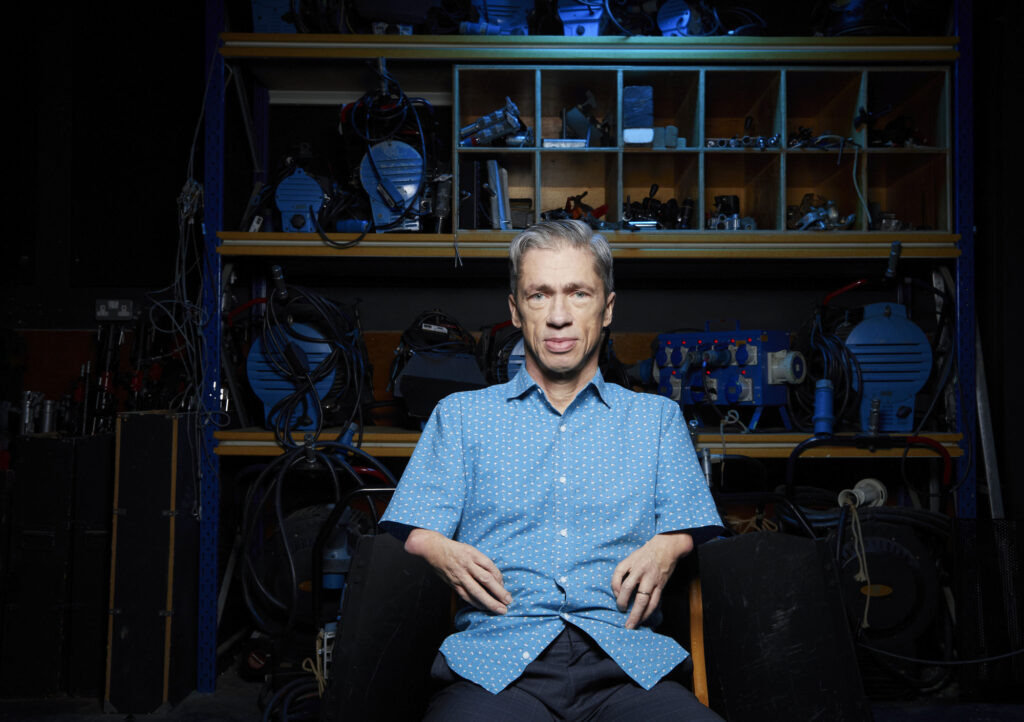 Photograph of a white man in his 50s with shortened arms sits in a blue shirt in a workshop space