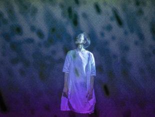 A Japanese woman in a white dress in blue/purple light.