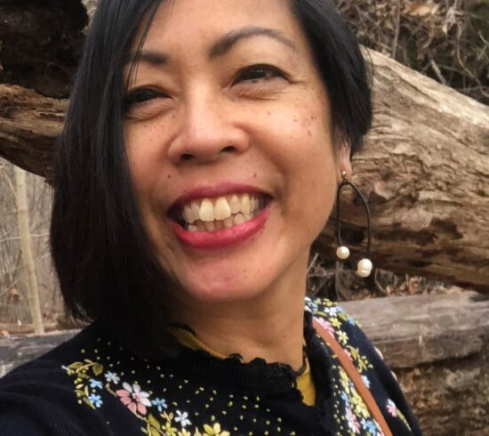 Photo portrait of Chanika Svetvilas, an Asian American woman with chin length black hair wearing pearl drop earrings and a black cardigan with small colorful embroidered flowers. A leaning tree trunk is in the background. Photo was taken during a hike in the woods.