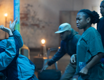 To the right, three young Black dancers in muted clothing watch a young white dancer in tracksuit and black baseball cap, who is positioned on the left of the image and dancing a mix of krump and BSL. The background is a warehouse brick wall.