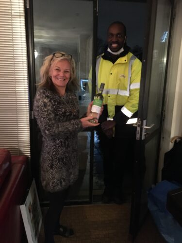 White woman in her 50s holding non alcoholic wine brought by a black Tesco Delivery Man
