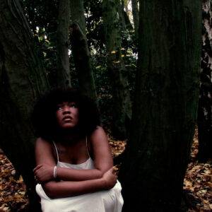 Still image of a black female artist sitting in a wood