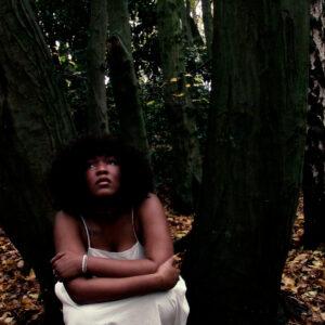 Still image of a black female artist sitting in a wood