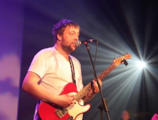 White learning disabled man performing with an electric guitar on stage in front of strobing lights