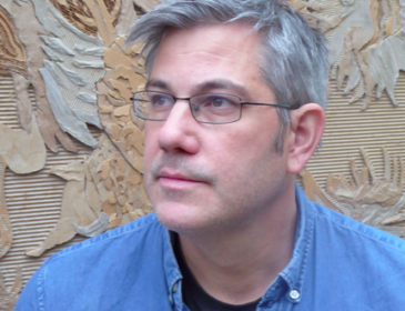 portrait photo of a man with thin rimmed glasses looking away from the camera with cardboard flowers in the background
