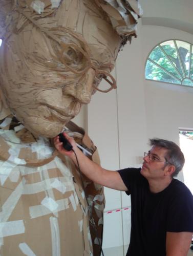 james working on an oversized cardboard sculpture of himself