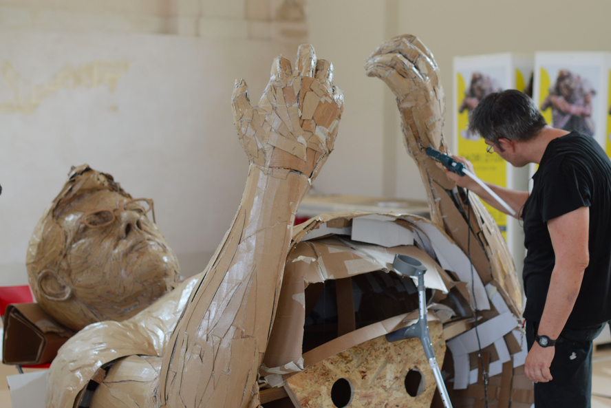 Film screen shot of white male artist working on a large sculpture