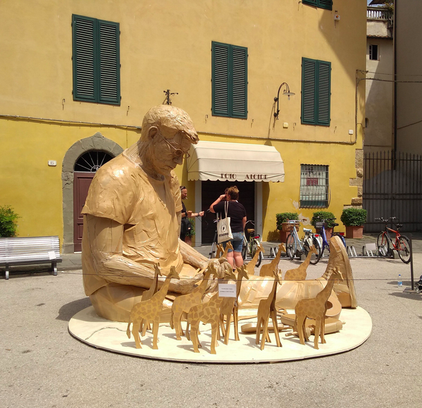 james' oversized cardboard sculpture of himself sitting in a piazza surrounded by cardboard giraffes
